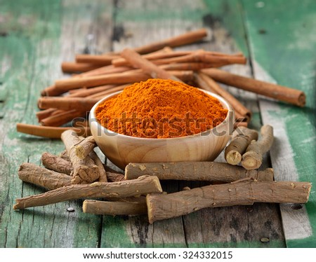 Licorice roots Cinnamon sticks and turmeric on wooden - stock photo