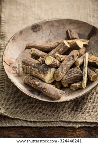 Licorice roots on wooden bowl on a jute bag - stock photo