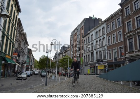 LIEGE, BELGIUM, APRIL 13, 2014: Belgian man in descending from the bridge on his bike in the center of Liege. - stock photo