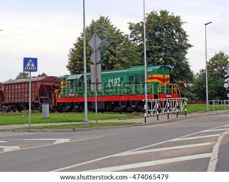 LIEPAJA, LATVIA - AUGUST 22, 2016: Diesel locomotive with cargo wagons is runing to railway and street crossing.