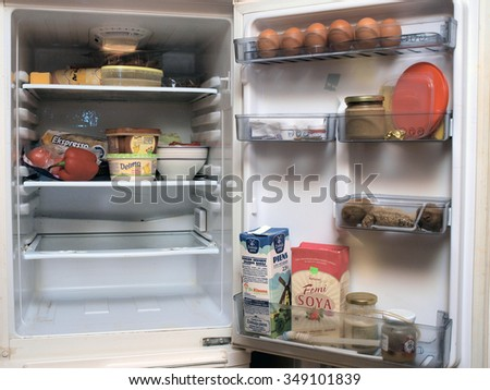 LIEPAJA, LATVIA - DECEMBER 7, 2015: Eggs and dairy products on shelves in small home fridge. - stock photo