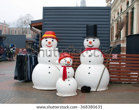 LIEPAJA, LATVIA - JANUARY 27, 2016: Central market pavilion entrance is decorated by three artificial snowman family. - stock photo