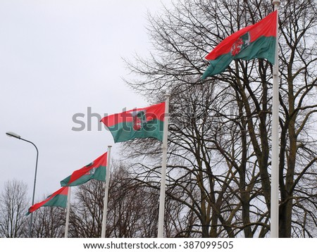 LIEPAJA, LATVIA - MARCH 2, 2016: Liepaja town flags are fluttering in wind on flagpoles.       - stock photo