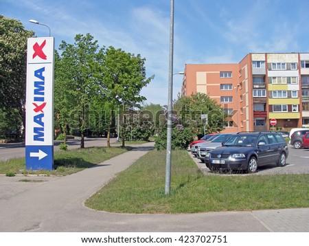 LIEPAJA, LATVIA - MAY 19, 2016: Car park at the apartment houses on Kalpaka street and sign pointing to supermarket Maxima. - stock photo