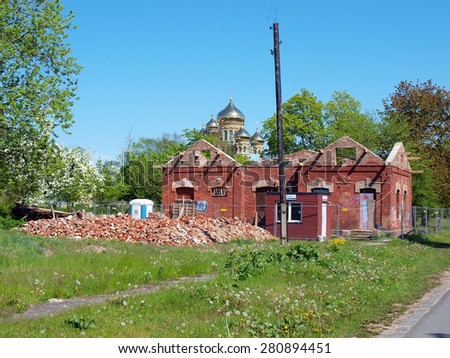 LIEPAJA, LATVIA - MAY 21, 2015: Gilded domes of cathedral are visible behind the ruins of red brick house.         - stock photo
