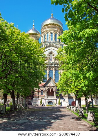 LIEPAJA, LATVIA - MAY 21, 2015: The gilded domes and side entrance of St. Nicholas Naval Orthodox Cathedral are visible behind the park trees. - stock photo