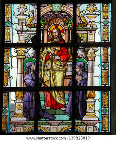 LIER, BELGIUM - MAY 25: Stained glass window depicting Jesus and two catholic nuns in the Church of the Beguinage in Lier, Belgium, on May 25, 2013. - stock photo