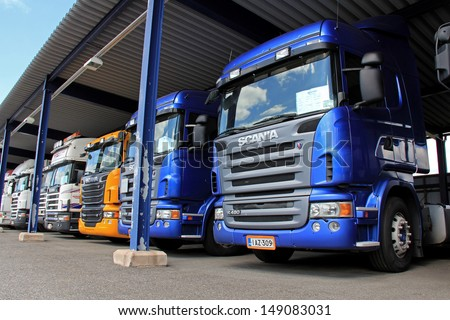 LIETO, FINLAND - AUGUST 3: Scania trucks in a carport in Lieto, Finland on August 3, 2013. Scania reports that two Scania trucks operated in China reached a mileage of 3 million kilometers. - stock photo