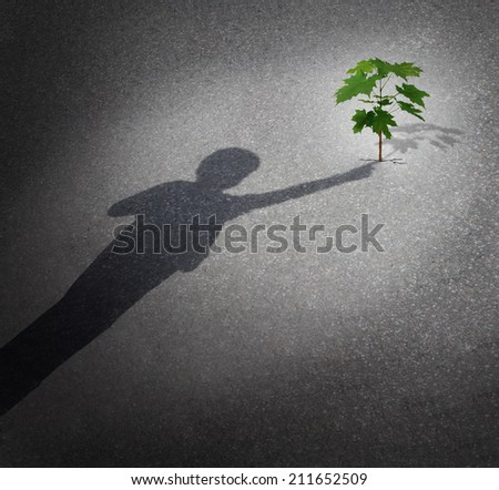 Life and hope as a grow concept with a shadow of a child touching a tree sapling growing through city pavement as an icon for the future environment protection and the support of the next generation. - stock photo