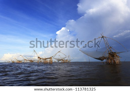 Life asian fisherman and bamboo machinery (square dip net)at canal. Klongyoun canal, Pattalung, Thailand. - stock photo