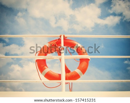 life belt (6), life buoy, red rescue ring on a ship against blue sky with clouds - stock photo