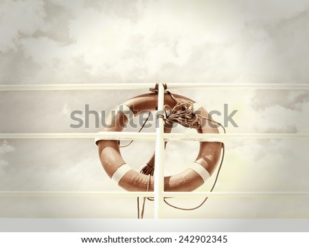 life belt, life buoy, red rescue ring on a ship against blue sky with clouds - stock photo