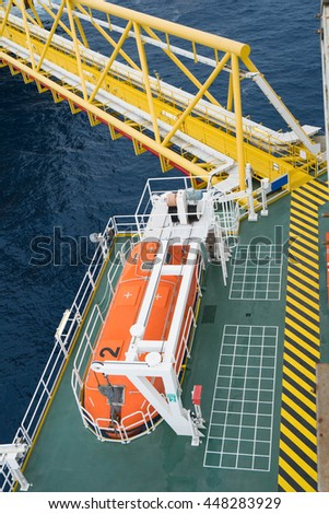 Life boat or rescue boat at muster point area near oil and gas processing platform bridge  - stock photo