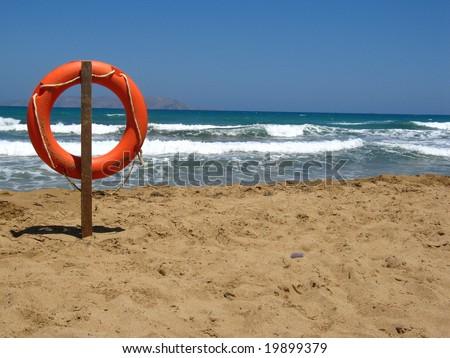 Life bouy in the empty beach of Crete, Greece - stock photo