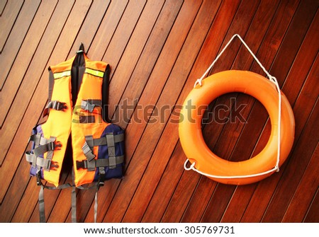 Life buoy and life jackets on wooden board - stock photo