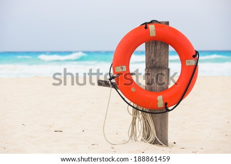 Life buoy attached to a wooden post at the beach in Mexico - stock photo