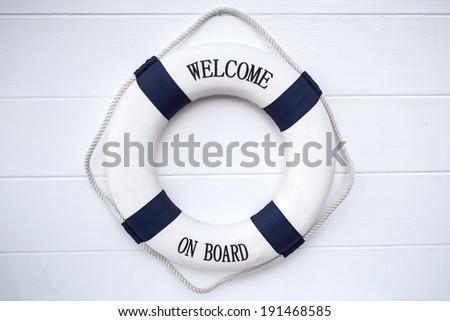Life buoy decoration on white wooden background - stock photo