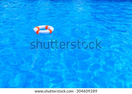 Life buoy floating in a swimming pool - stock photo