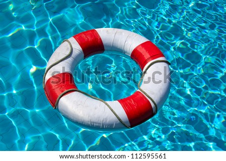 Life buoy in blue swimming pool - stock photo