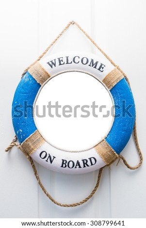 Life buoy mirror isolate with welcome on board on white wood door - stock photo