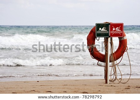 Life buoy on a beach against the sea. Rainy weather. - stock photo