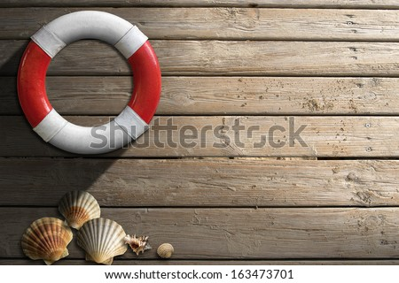 Life Buoy on Wooden Wall with Seashells / Red and white lifebuoy hanging to a wooden wall with seashells and sand - stock photo