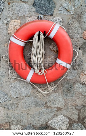 Life buoy ring hanging on rock wall - stock photo