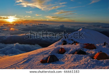 Life in tents above the clouds, at sunset (over Refuge du Goûter Mont Blanc - France) - stock photo