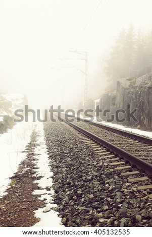 Life is a journey as a thought. Image of an empty railroad taken from low point of view. A thick fog is filling the atmosphere. Also image has a vintage effect.