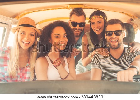 Life is better when friends are near. Group of joyful young people smiling at camera while sitting inside of minivan together