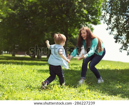 Life moment of happy family! Mother and son child playing having fun together on the grass in sunny summer day - stock photo