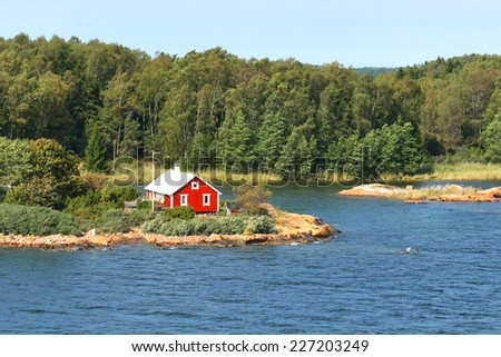 Life on small island. Red house on rocky shore of Baltic Sea. Aland Islands, Finland - stock photo