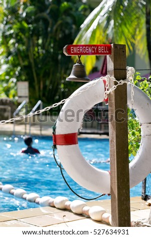 Life preserver white red lifebuoy hanging next to swimming pool