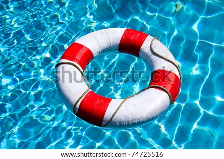 Life ring floating on top of sunny blue water - stock photo
