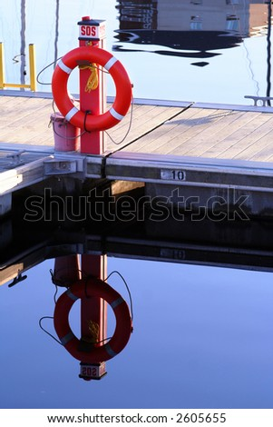 Life ring on a marina cat walk reflected in still water - stock photo