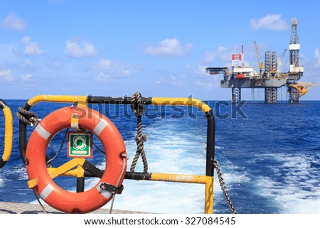 life ring on the offshore supply boat with Jack up drilling rig background - stock photo