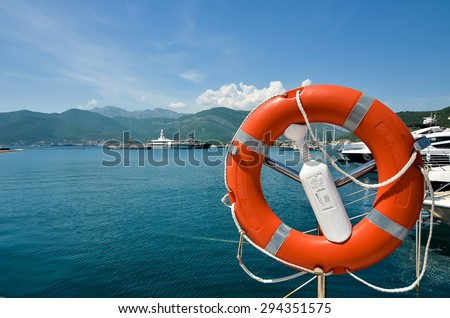Life ring with sea and mountains in the background - stock photo