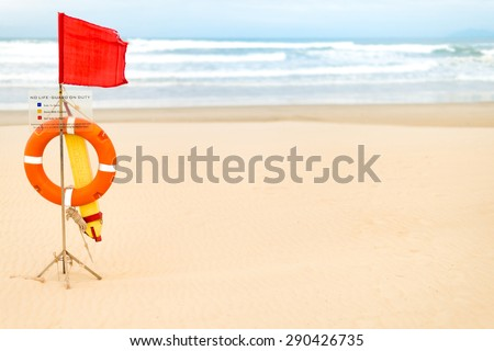 "Life saving devices hanging on wooden rack with red flag and warning table ""no life-guard on duty"" on empty beach. Ocean and blue sky in background. Safety and caution measures during swimming."