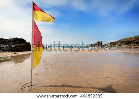 Life saving flags and beach at trevone in cornwall england uk.