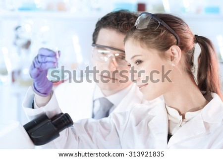 Life scientist researching in laboratory. Attractive young scientist and her post doctoral supervisor looking at the microscope slide in the forensic laboratory. Healthcare and biotechnology. - stock photo