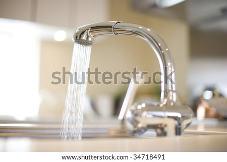 LIFE STYLE-a kitchen faucet with water flowing - stock photo