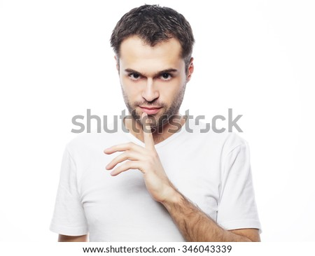 life style  and people concept: young man wearing white t-shirt making silence gesture, shhhhh!!