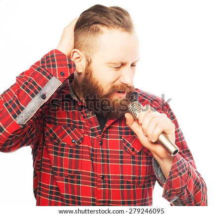 Life style concept: a young man with a beard wearing a white shirt holding a microphone and singing. Hipster style. Over white background. - stock photo