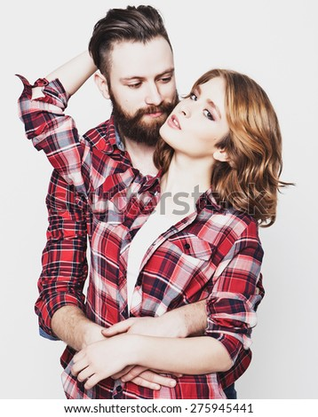 life style, happiness and people concept: Hipster couple. Beautiful young loving couple pposing  while standing against white  background. - stock photo