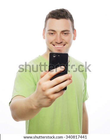Life style, tehnology and people concept: a young man in shirt holding mobile phone and making photo of himself while standing against white background. - stock photo