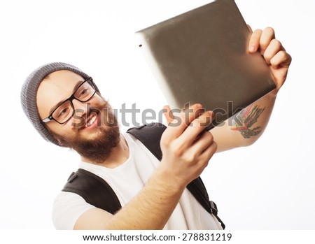 life style, tehnology and people concept: Happy selfie. Young bearded man holding tablet and making photo of himself while standing against white background - stock photo