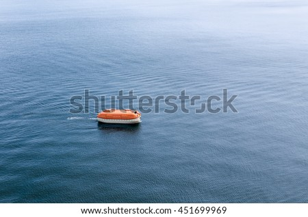 Lifeboat awaiting rescue in the wide expanse of the sea. Life boat is enclosed and rigid type rescue craft. - stock photo