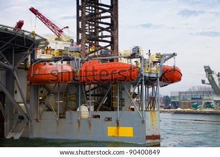 Lifeboats on an oil rig. - stock photo