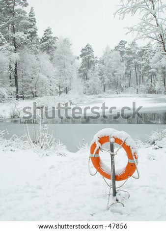 Lifebuoy at frozen pond - stock photo