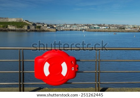 Lifebuoy enclosed in plastic cover hanging on the pier in Plymouth, UK. - stock photo